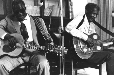 Rev. N.L. Williams playing blues guitar while